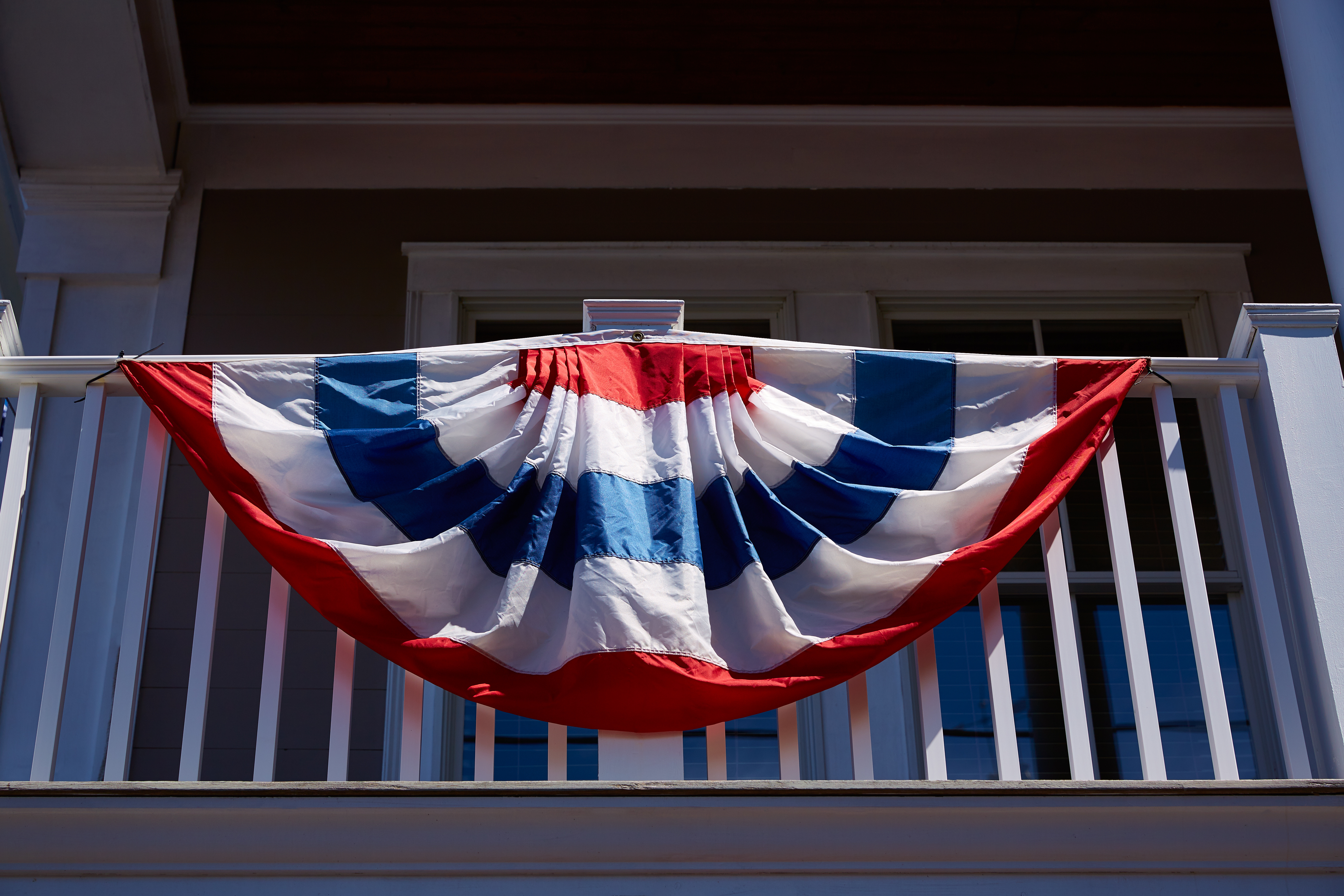 blog image of american flag on an apartment balcony; blog title: 3 Ways to Celebrate the True Meaning of Memorial Day