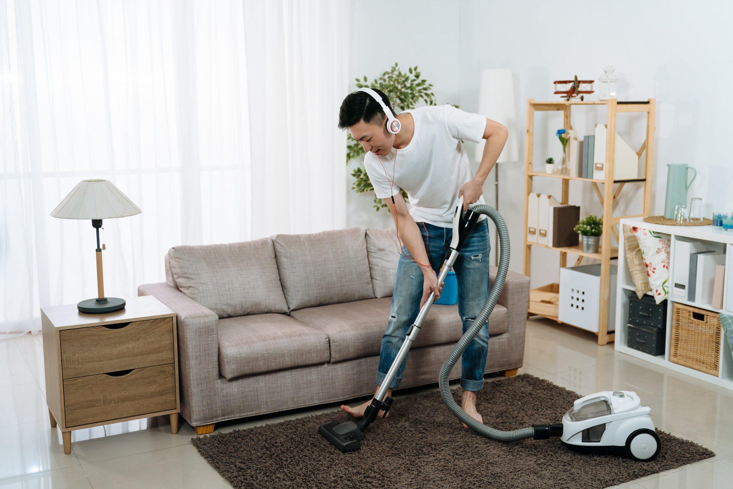young man vacuuming his apartment