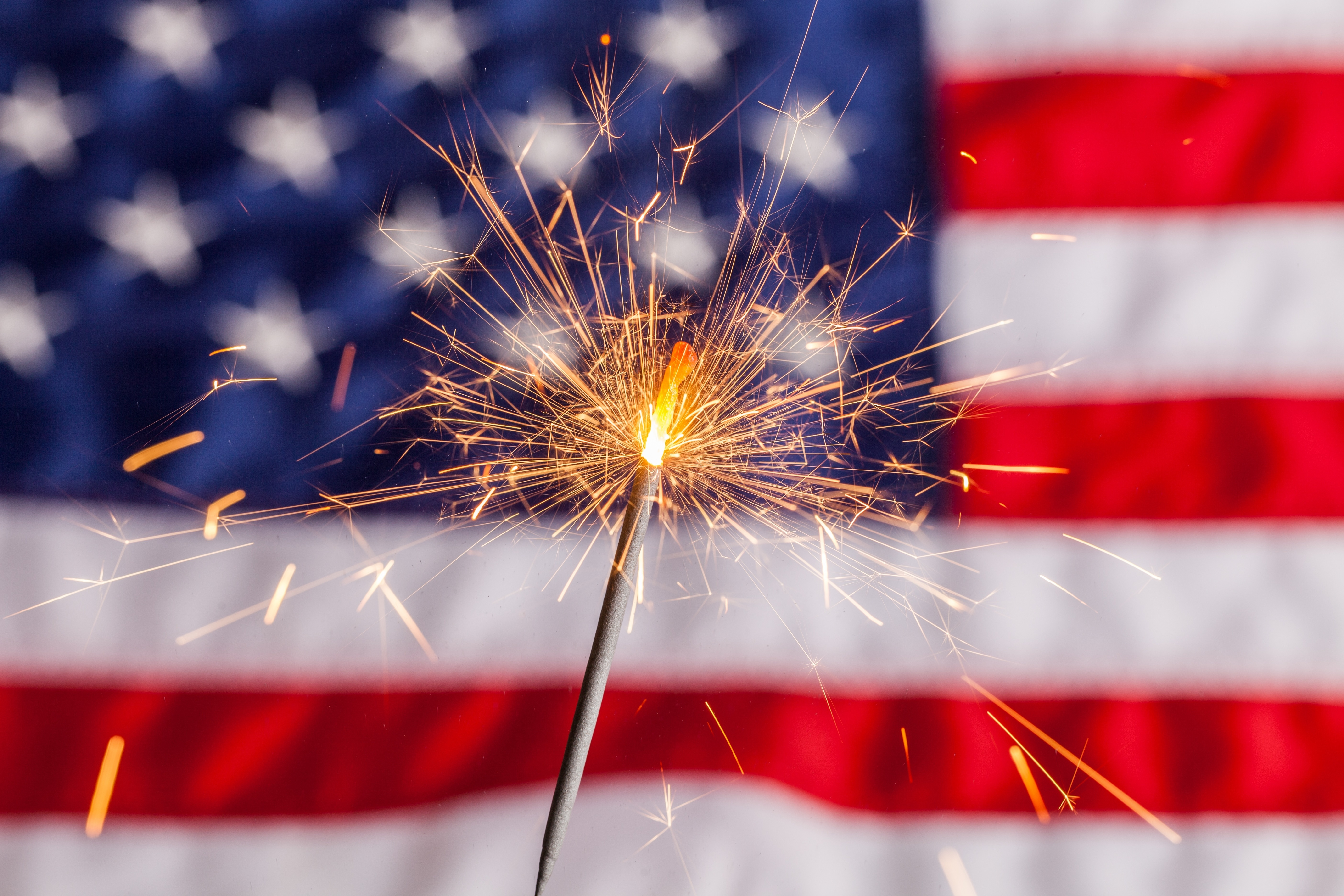 blog image of a sparkler in front of an american flag; blog title: Enjoy A Safe and Fun Fourth of July at Your Apartment