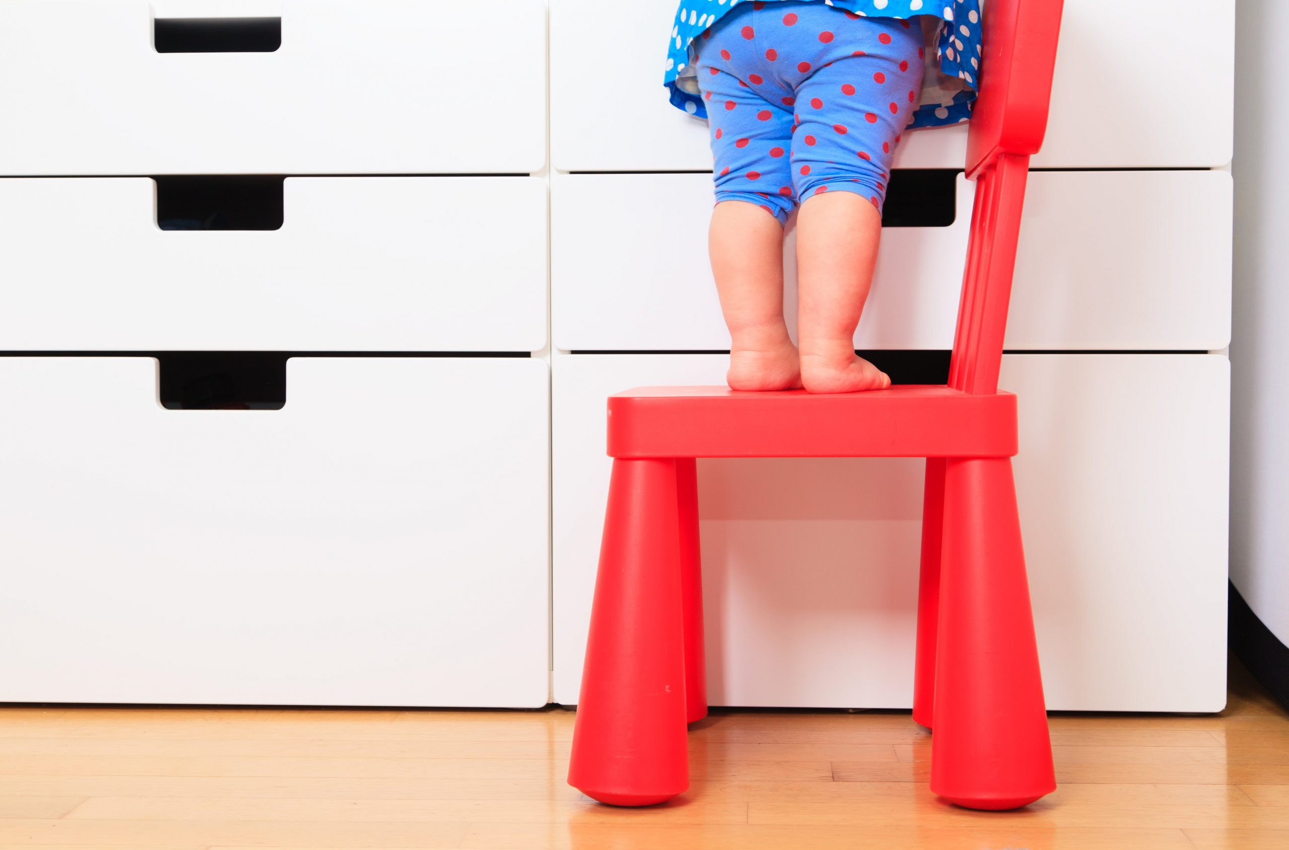 blog image of a child standing on a chair to reach something dangerous on the dresser